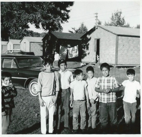 a black and white photo showing a group of children in front of cabins